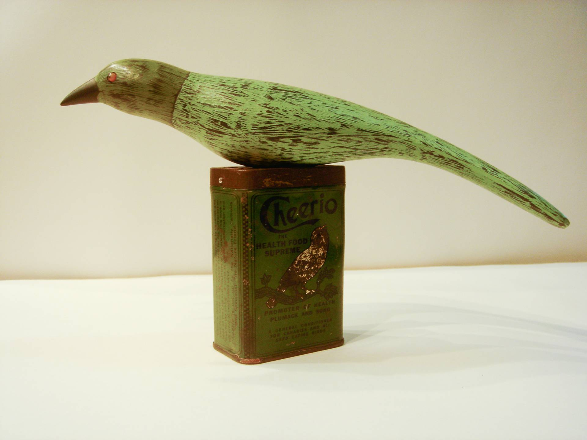 hand crafted wooden bird textured and painted gesso on poplar with antique bird food tin base