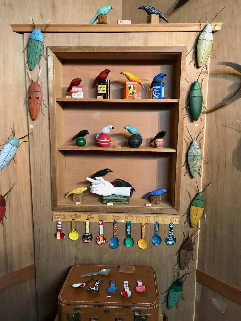 2019 ACE booth back right corner with hand carved birds, wooden bugs and tin coffee measures