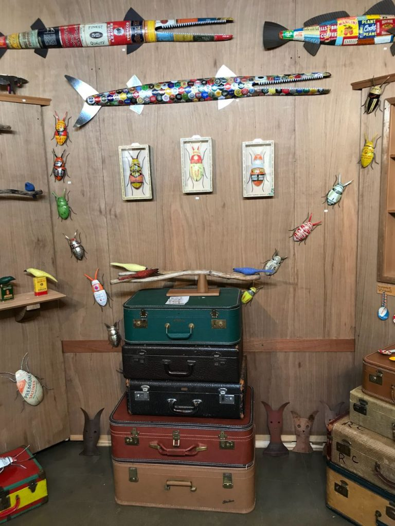 2019 Richmond Craft + Design Booth back wall with hand-carved birds, metal bugs, and metal-clad & bottle cap fish.