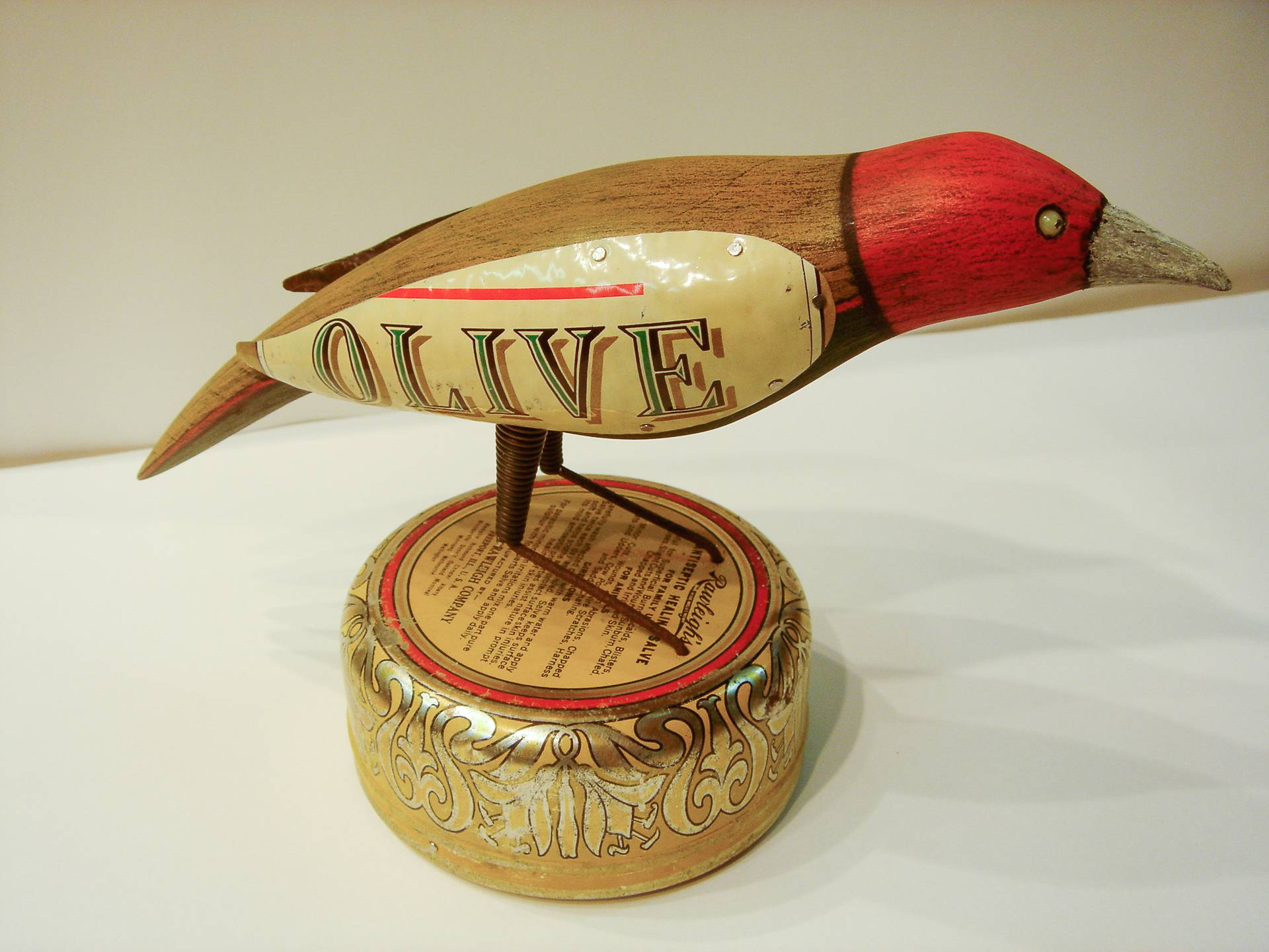 hand crafted colored bird sculpture with antique tobacco tin wings