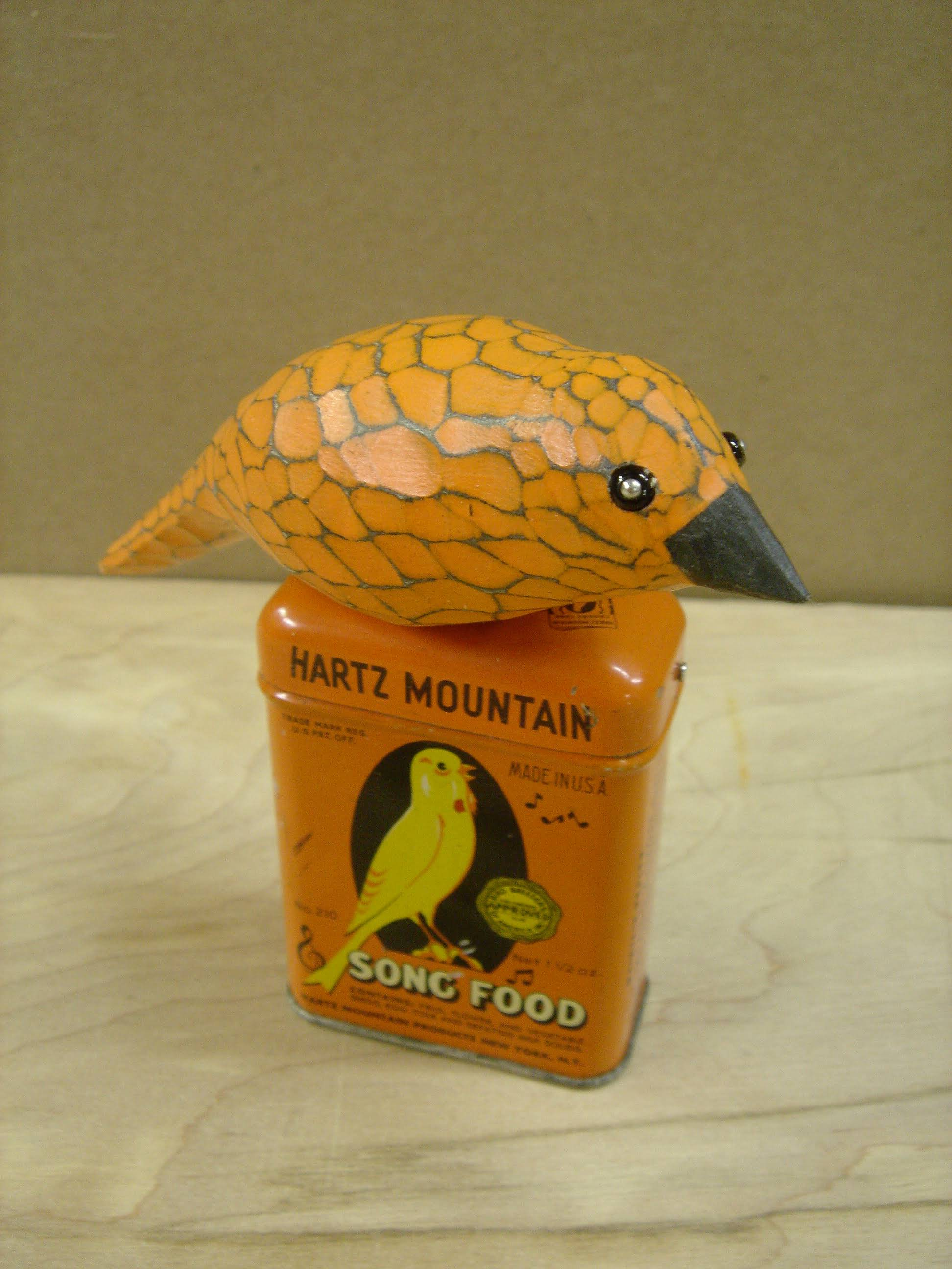 hand carved and painted pine bird on antique bird food tin