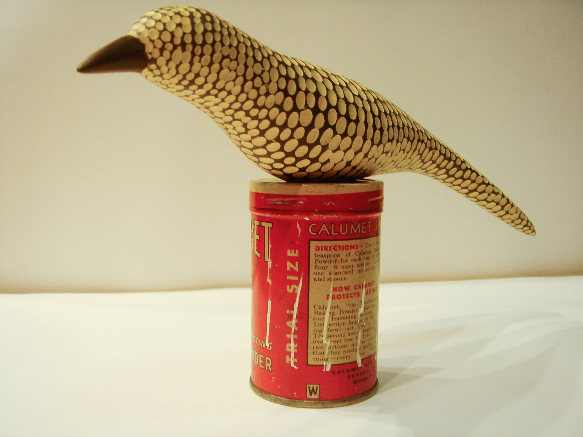 hand crafted wooden bird textured and painted gesso on poplar with antique baking powder tin base